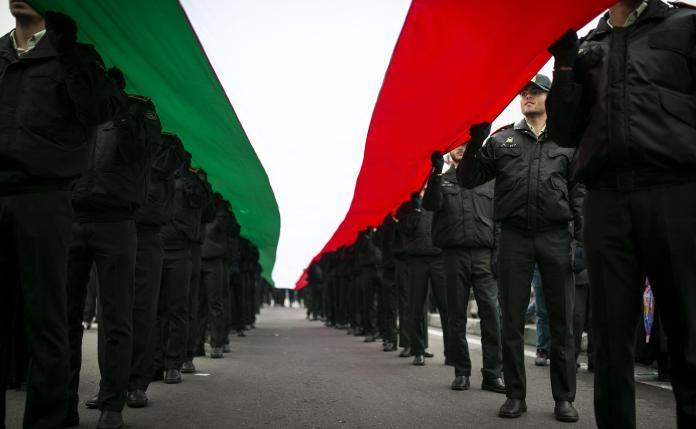men in black uniform holding a green white and red flag