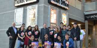 people stand in front of ticket office and some hold COCO movie posters