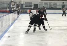 CSUN hockey player defends puck from opponent