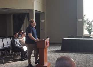 man in blue shirt speaking at podium