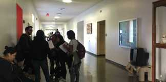 students stand around in a hallway