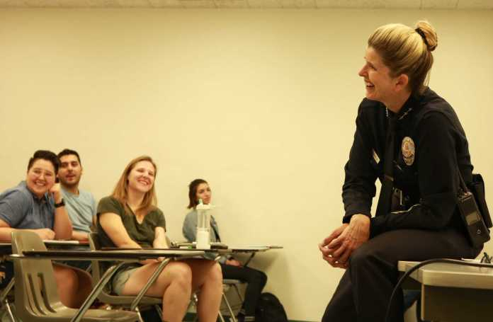 Police officer laughing while speaking to students