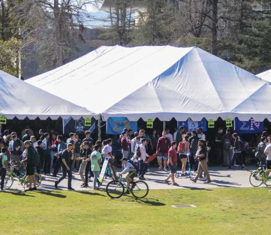 large white tents with many students surrounding them