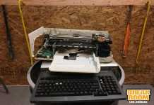 torn apart printer on top of old typing keyboard