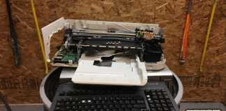 torn apart printer on top of old typing keyboard