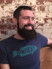 "A light-skinned man from the shoulders up, reclining against a brick wall. He is smiling, has dark hair and a beard, and is wearing a blue t-shirt with a fish on it and the word ""Kentucky."""