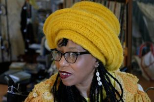 A black woman wearing a crocheted yellow top and yellow hat, taken from the shoulders up. Her hair is in braids and she is wearing a cowrie shell earring. She is wearing glasses and looking off to the side.