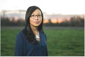 Asian woman with black glasses and long black hair and navy blouse, viewed from waist up, standing in grassy field with sunset in horizon.