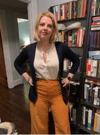 White woman with shoulder-length blonde hair standing in front of bookshelf with both hands on hips, wearing navy cardigan, cream blouse, and orange pants