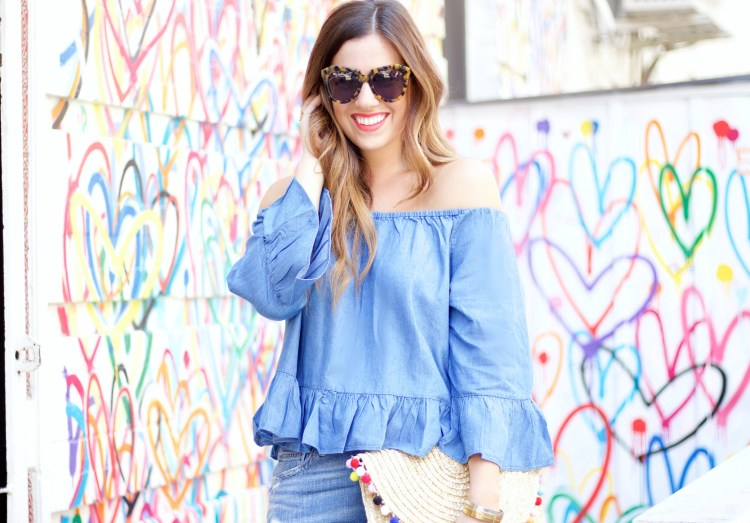 Jaime Cittadino of Sunflowers & Stilettos wearing a Goodnight Macaroon chambray off-theshoulder top and pom pom straw clutch in Soho NYC
