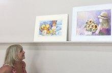 Joyce Ennis admires paintings awaiting critiques