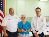 "Sun Lakes Fire District Chief Troy Maloney (left) and Deputy Chief Rob Helie (right) presented a token of appreciation plaque to the Sun Lakes Women's Association for their many years of support. Accepting the award for the association was President Collette McNally. Maloney thanked the women for their ""unwavering generosity and philanthropy with the Fire District and the Sun Lakes community."" McNally commented that the SLWA was founded to help support the beginnings of what was then the Sun Lakes Fire Department when it was manned by all volunteers. (Photo and caption by Brian Curry),"