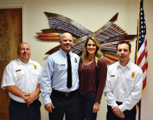 SLFD Chief Troy Maloney (left) and Deputy Chief Rob Helie (right) pose with newly-promoted Captain Nate Stringfellow with his wife Rochelle after his badge pinning.