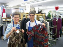 Sun Lakes residents Nancy Smith (left) and Barb Dubler display boutique clothing for sale in the new Assistance League of East Valley thrift shop. Proceeds clothe 7,500 needy schoolchildren.