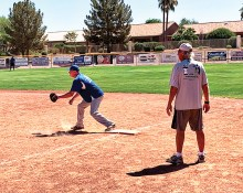 """First baseman Dean Messier awaits a throw while first base coach """"Hoot"""" Gibson looks on. (Photo by Core Photography)"""
