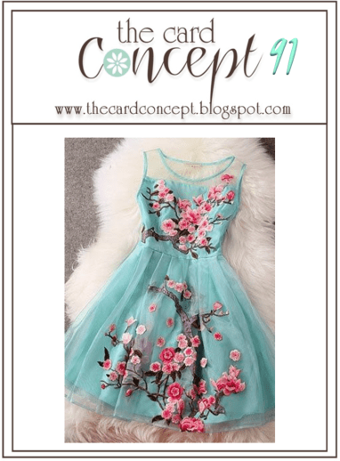 The Card Concept Inspirational Photo featuring a blue dress with pink flowers on branches laid out on a cream fur rug.