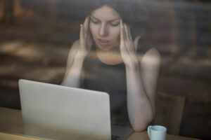 Woman with headache holding temples, sitting in front of laptop.