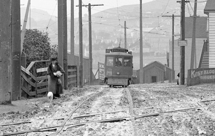 1912, detail from previous photo. Woman with dog waits for the the electric streetcar just south of the Sunnyside crossing. Photo courtesy SFMTA sfmta.photoshelter.com.