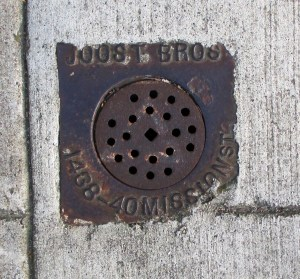 Joost Bros branded sewer vent, minted before the 1906 Quake with the old store location, but installed on this sidewalk on Bosworth Street in the 1920s.