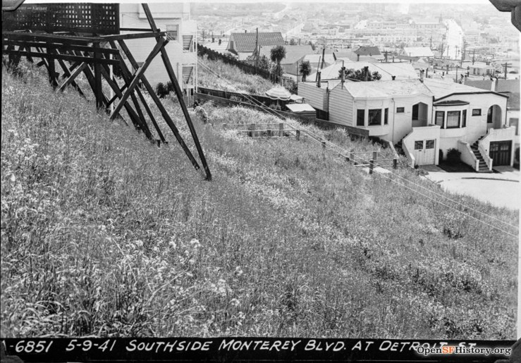 1942. View of Lower Detroit Steps (the bannisters at least) from vacant lot that is current site of 401-407 Monterey Blvd. House at 397 Monterey/450 Detroit St visible on far left; 420 - 414 Detroit on right. OpenSFHistory.org