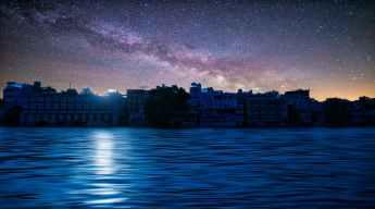 city near body of water under a starry sky