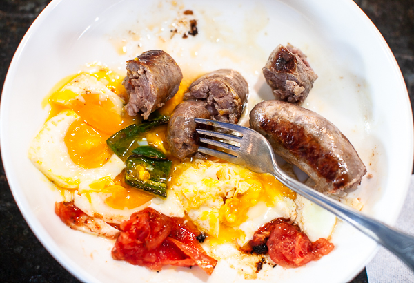 plate with half eaten sausages, eggs, chili, tomato and fork