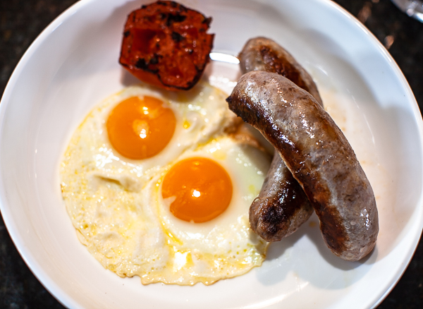 plate of two sunny-side eggs, grilled tomato and two English Banger sausages