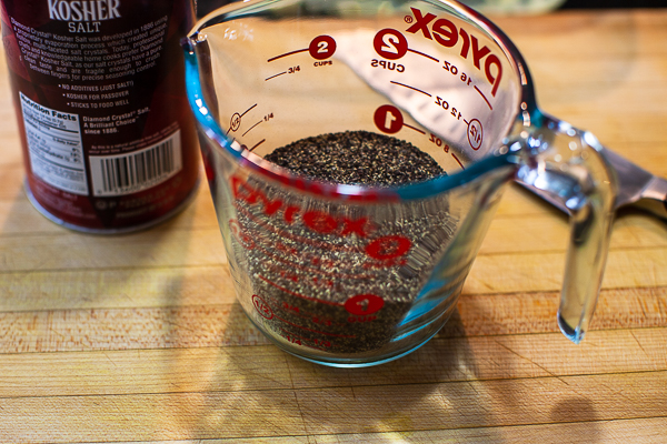 glass measuring cup containing pepper, salt container sitting on wooden cutting board