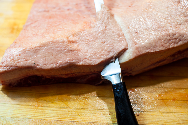 slicing fat off the top of a brisket