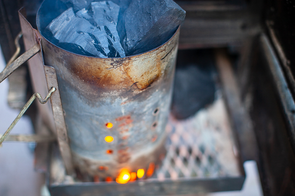charcoal burner with coals on top, glow of flame in bottom sitting on mesh tray