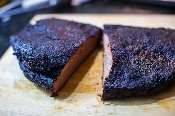 dark smoked brisket on cutting board, cut in half through the middle width