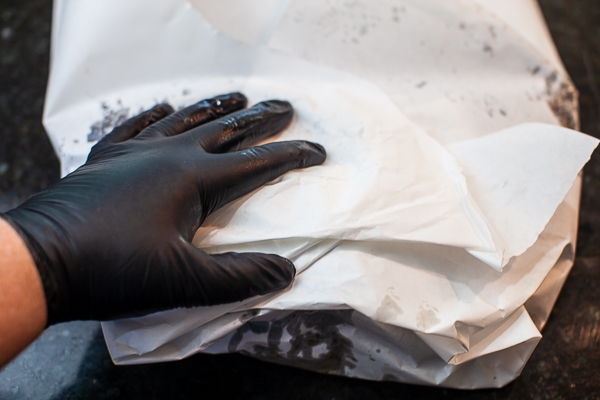 black gloved hand on top of brisket wrapped in white butcher paper