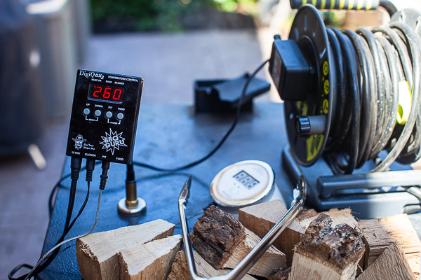 thermometer reading 260 degrees F, wood chunks, tongs, extension cord on top of smoker