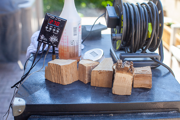 Thermometer reading 270 degree F, wood chunks, spray bottle of apple cider vinegar/water mixture, extension cord on top of smoker
