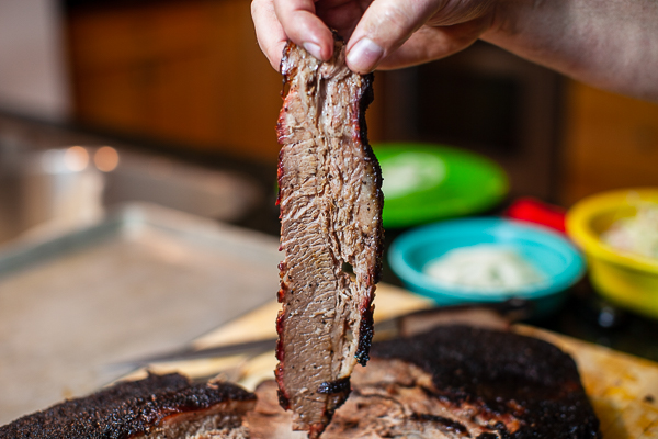 Hand holding slice of brisket vertically with bowls of condiments in the background