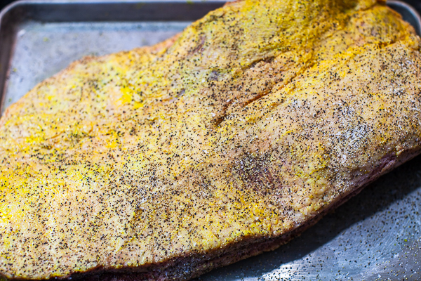 uncooked top of brisket slathered with mustard and sprinkled with salt and pepper