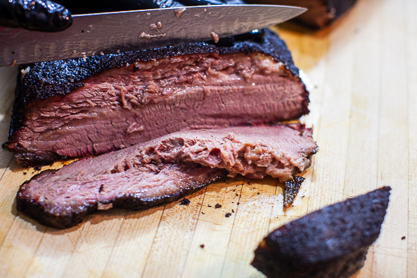 Slicing smoked brisket on wooden cutting board