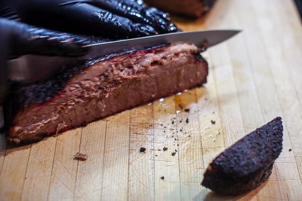black gloved hand holding sharp knife cutting through brisket on wooden cutting board