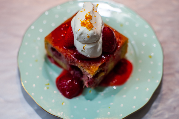 square of strawberry financier cake with strawberry compote and whipped cream on plate