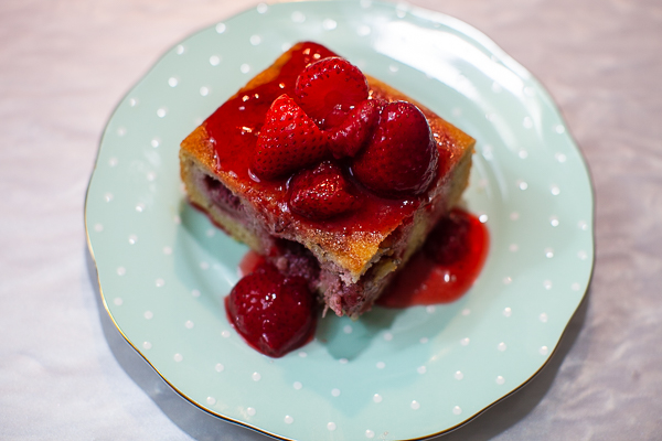 square of strawberry financier cake topped with strawberries and compote on plate