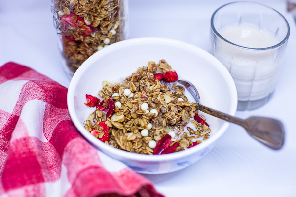 bowl of granola contining white chocolate pearls and dried strawberries with red and white checkered napkin, glass of milk and glass jar of granola