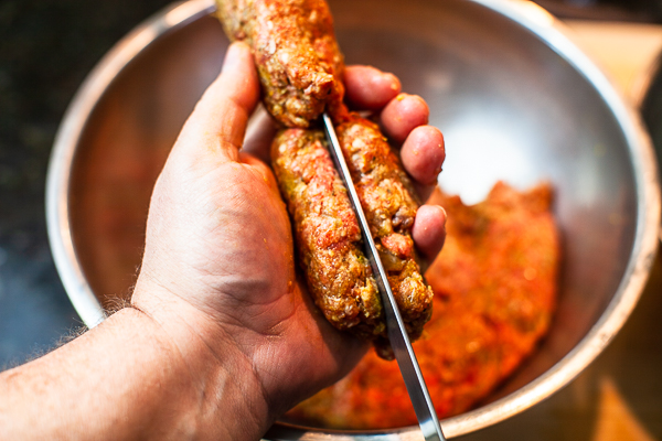 meat mixture being in palm of hand being pressed around flat metal skewer