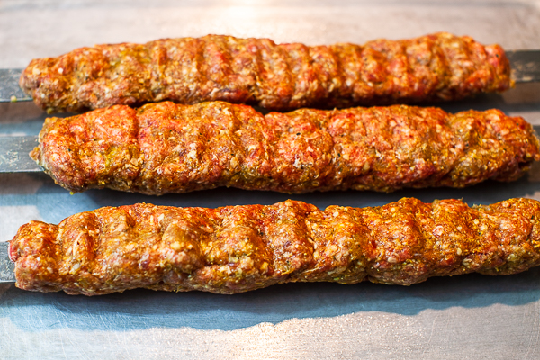 three kebabs (meat mixture around flat metal skewers) on cookie sheet