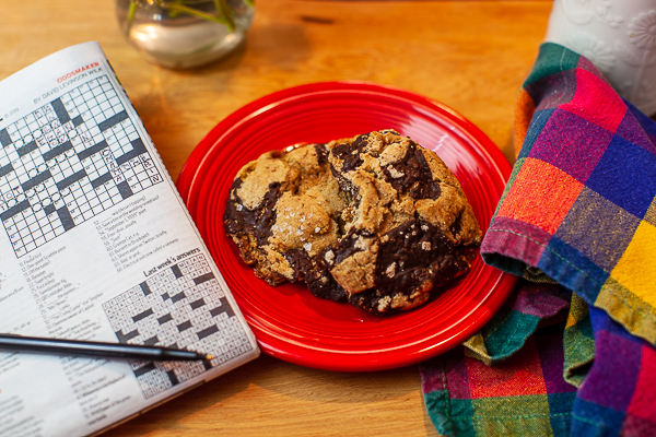 Cookie on plate with crossword puzzle and napkin on cutting board in background