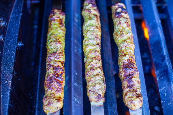 three slightly charred kebabs over low-medium flame