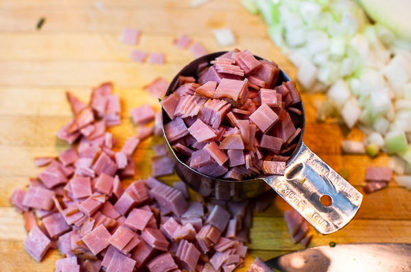 one cup of diced ham on a wooden cutting board