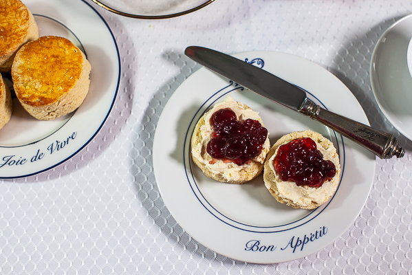 plate with halved english scone, clotted cream and strawberry jam