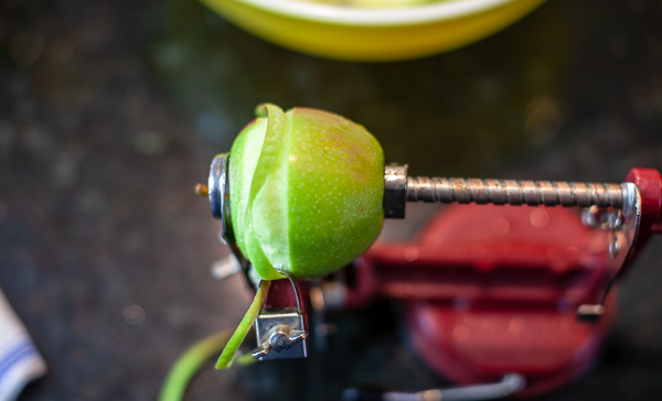 apple being cored and peeled by table top apple peeler