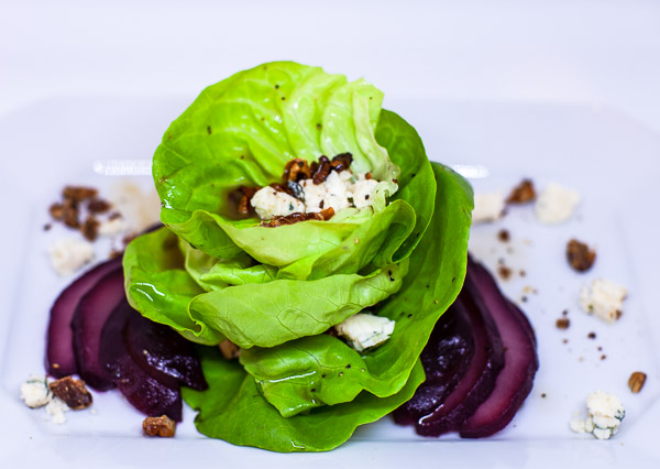 salad tulipe layered with roasted walnuts,blue cheese, drizzled with dressing and surrounded by poached pears