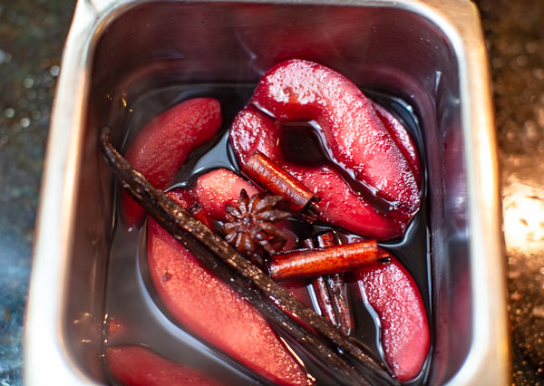 pan with wine, poached pears, anise, cinnamon sticks, vanilla bean